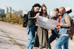 группа в составе многокультурные молодые друзья выбирая назначение стоковое изображение rf