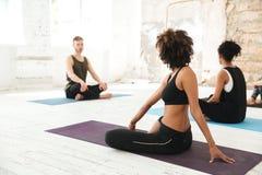 Группа в составе многокультурное молодые люди практикуя йогу Стоковое фото RF