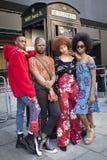 Группа в составе модно одетые друзья беседуя на входе к зданию стоковые изображения