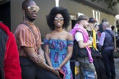 Группа в составе модно одетые друзья беседуя на входе к зданию стоковое фото