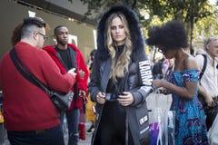 Группа в составе модно одетые друзья беседуя на входе к зданию стоковая фотография
