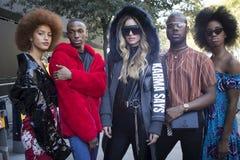 Группа в составе модно одетые друзья беседуя на входе к зданию стоковые фотографии rf
