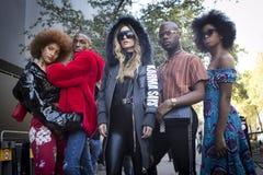 Группа в составе модно одетые друзья беседуя на входе к зданию стоковая фотография rf