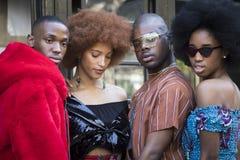 Группа в составе модно одетые друзья беседуя на входе к зданию стоковое фото rf