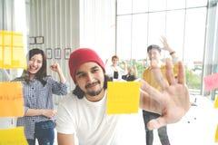 Группа в составе молодая успешная творческая многонациональная команда усмехаясь и коллективно обсуждать совместно во встрече Смо стоковое фото rf