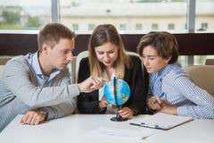 Группа в составе молодой поиск глобуса исследования студентов для страны перемещения Стоковые Изображения RF