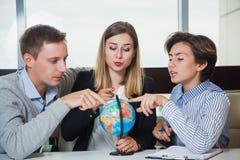 Группа в составе молодой поиск глобуса исследования студентов для страны перемещения Стоковая Фотография
