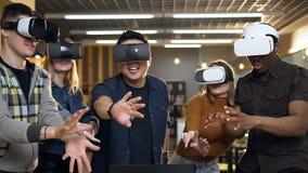 Группа в составе молодой multi этнические человек и женщина имея потеху используя стекла виртуальной реальности vr видеоматериал