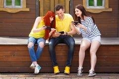 Группа в составе молодость смеясь над играя передвижную видеоигру outdoors Стоковые Фотографии RF