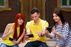 Группа в составе молодость смеясь над играя передвижную видеоигру outdoors, парень Стоковая Фотография