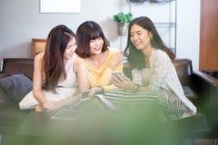 Группа в составе молодые азиатские женские друзья в кофейне, используя цифровые приборы, беседуя с smartphones стоковое фото rf