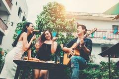 Группа в составе молодые азиатские люди счастливые пока наслаждающся домашней партией и стоковые изображения