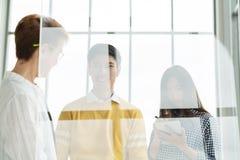 Группа в составе молодые азиатские привлекательные бизнесмены стоя, говоря и слушая к встречать менеджера за прозрачным стеклом w стоковые изображения