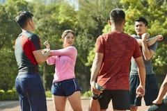 Группа в составе молодые азиатские спортсмены протягивая ноги и оружия стоковая фотография rf