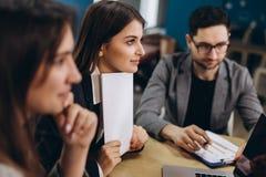 Полная концентрация на работе Группа в составе молодые бизнесмены работая и связывая пока сидящ на столе офиса совместно стоковые фото