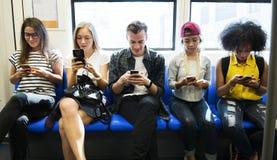 Группа в составе молодые взрослые друзья используя smartphones в метро стоковое фото
