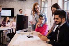 Группа в составе молодые дизайнеры перспективы обсуждая в офисе Стоковое фото RF