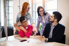 Группа в составе молодые дизайнеры перспективы обсуждая в офисе Стоковое Изображение