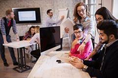 Группа в составе молодые дизайнеры перспективы обсуждая в офисе Стоковая Фотография