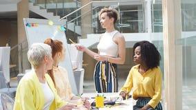 Группа в составе молодые дизайнеры сотрудничая на проекте в офисе акции видеоматериалы