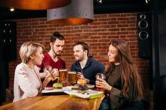 Группа в составе молодые друзья встречая в кафе Стоковое Изображение