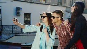 Группа в составе молодые друзья - один человек и 2 женщины делая selfie видеоматериал
