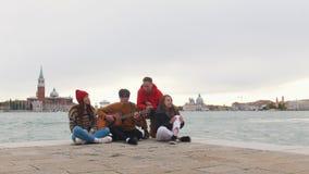 Группа в составе молодые друзья сидя на краю песен набережной и петь Человек играя гитару акции видеоматериалы