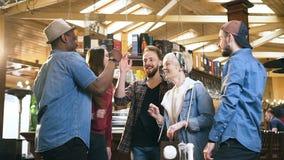 Группа в составе молодые друзья хипстера приветствуя один другого в пабе, баре видеоматериал