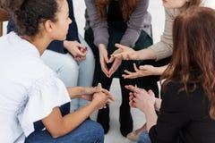 Группа в составе молодые женщины говоря усаживание в круге Психологическая концепция поддержки стоковые изображения