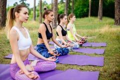 Группа в составе молодые женщины практикуя йогу outdoors Стоковое фото RF