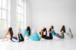 Группа в составе молодые женщины приниманнсяый за протягивать в спортзале r стоковая фотография rf
