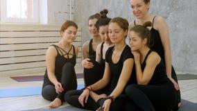 Группа в составе молодые женщины принимая selfie используя сотовый телефон на занятиях йогой Стоковое фото RF