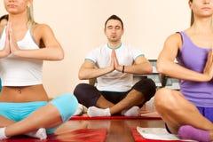 Группа в составе молодые люди делая йогу Стоковая Фотография