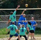 Группа в составе молодые люди играет волейбол пляжа на выходных Стоковые Фотографии RF