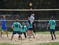 Группа в составе молодые люди играет волейбол пляжа на выходных Стоковые Фото