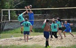 Группа в составе молодые люди играет волейбол пляжа на выходных Стоковая Фотография RF