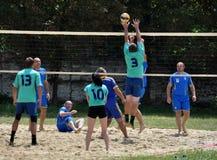 Группа в составе молодые люди играет волейбол пляжа на выходных Стоковое Изображение