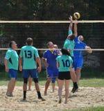 Группа в составе молодые люди играет волейбол пляжа на выходных Стоковая Фотография