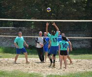 Группа в составе молодые люди играет волейбол пляжа на выходных Стоковое Изображение RF