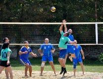 Группа в составе молодые люди играет волейбол пляжа на выходных Стоковые Изображения RF