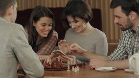 Группа в составе молодые люди играя шахмат и используя smartphone Стоковые Фото