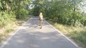 Группа в составе молодые люди идет неторопливой на велосипедах в парке и снимает видео на камере gopro видеоматериал