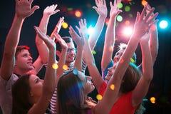Группа в составе молодые люди имея танцы потехи на партии стоковое фото