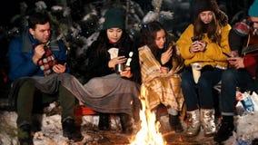 Группа в составе молодые люди в лесе зимы сидя огнем Люди сидя в их телефонах и фотографируя видеоматериал