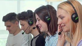 Группа в составе молодые люди нося шлемофоны, работая в центре телефонного обслуживания сток-видео