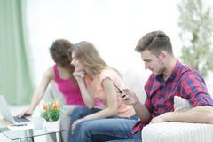 Группа в составе молодые люди отдыхая на кресле в живущей комнате Стоковые Изображения
