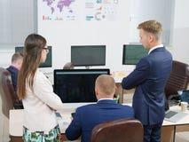Группа в составе молодые люди в офисе смотря экран компьютера Стоковое фото RF