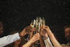 Группа в составе молодые люди празднуя Новый Год с шампанским на ночном клубе Стоковое фото RF