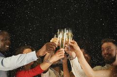 Группа в составе молодые люди празднуя Новый Год с шампанским на ночном клубе Стоковая Фотография RF