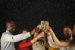 Группа в составе молодые люди празднуя Новый Год с шампанским на ночном клубе Стоковая Фотография